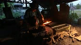 arma : Professional Blacksmith at work is Hit the iron by a hot metal With fire