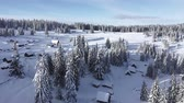 rumunia : Snow covered remote village, homestead in the mountains. 4K aerial drone view