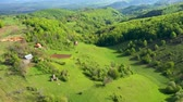 домик : Flying above green countryside hills and village houses, farmland in the spring. Aerial 4k drone view