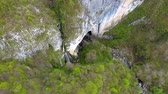gruta : Aerial 4k view of a waterfall and big cave entrance by drone