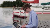 pó : young businessman working in nontraditional place marina . confident entrepreneur remote work near sailboat