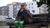 fácil : positive young man putting on earphones when sitting on the bench, mid shot Stock Footage