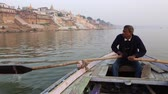 varanasi : Varanasi, India, December 2015. A man rowing in a rowboat on the river Ganges at sunset. Stock Footage