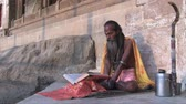 varanasi : Varanasi, India, October 2011: Sadhu reading a sacred book in a ghat on the Ganges River.