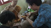 estrondo : Nakhon Chai Si, Thailand, March 2012: Buddhist monk tattooing a man in Wat Bang Phra. Stock Footage
