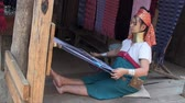 długi : Mae Hong Son, Northern Thailand, March 2012: Woman working on a handloom in the Burmese Karen refugee village known for its long-neck women.