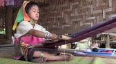 giraffe : Mae Hong Son, Northern Thailand, March 2012: Girl working on a handloom in the Burmese Karen refugee village known for its long-neck women.
