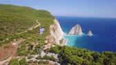 4K aerial view of Greek national flag waving in the sky in Keri in Zakynthos (Zakynthos) island in Greece