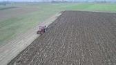 Agriculture and farming - Tractor plough a field in early spring aerial footage