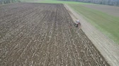 agronomia : Agriculture and farming - Tractor plough a field in early spring aerial footage