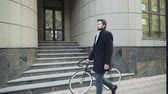 coat : handsome businessman walking with his bicycle in downtown
