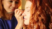 batom : time in a beauty salon. redhead young woman in a beauty salon. Stylist makes makeup bride on the wedding day. cosmetic powder brush for make up.