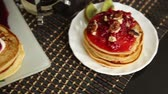 оладья : Homemade sweet pancakes with fruit jam, sour cream on a white plate. Breakfast with stack topped blueberry jam and walnuts.