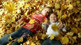 sister : Children lie in the yellow autumn leaves Stock Footage
