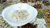 food and drink : In the bowl of muesli backfilled against the background of a variety of dried fruits and nuts. Slow Motion