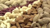 sugar pod : Moving past the camera portion of dried nuts - hazelnuts, peanuts, cashews, almonds, walnuts, pistachios, pecans, sunflower seeds and pumpkin Stock Footage