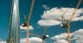 высокий : Tower Cranes on the Big Construction. Time Lapse. Many Tower Cranes work on the backdrop of a raised high-rise building and fast-moving clouds