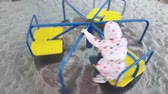 kolotoč : Cute happy little girl playing on a merry go round
