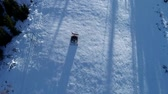 groomer : Aerial top down view of a snowcat or snow groomer on a ski resort slope in winter