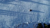 declive : Aerial top down view of a snowcat or snow groomer on a ski resort slope in winter