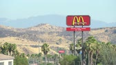 mcdonalds : Mc Donalds sign in the desert with mountains and palm trees - August 2017: near to Visctorville, California