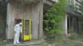 atomik : Man using a geiger counter with gas mask and protective suit in Pripyat. Slider shot 30km Chernobyl, exclusion zone