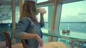 slider bar : Woman sitting in coffee shop on a cruise ship. Girl enjoying luxury cruise liner Stock Footage