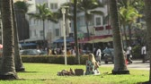 south american : Miami beach cityscape, street view. Girl sitting in the Lummus park at Ocean dr