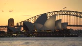 akşam vakti : Stunning view of the Sydney Opera House and Harbor bridge at sunset Stok Video