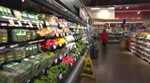 grocer : Woman shopping in grocery store, supermarket. Food on the shelf - United States
