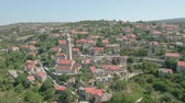 bell tower : Aerial view of a cozy mediterranean village between the mountains - Lozisca, Cro Stock Footage