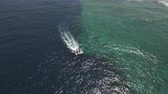 fast moving : Aerial view of a motorboat with scuba divers, near to coral reef