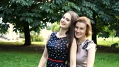 menopauza : Closeup Portrait of Adult Daughter and Mother Outdoors. Pretty Brunette and Her Mom are Looking at the Camera in the Park in Summer. Wideo