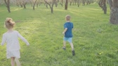 game field : Active boy and girl run near the trees in the park. Beautiful nature. Slow motion