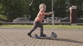 lambreta : little lovely boy on the kick scooter in the park. Slow motion