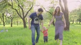 encourager : Beautiful family enjoying summer day in the park: little baby learning how to walk with mom and dad helping him to make his first steps Vidéos Libres De Droits
