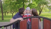 vínculo : Happy young parents share kiss their cute baby boy outdoors in park