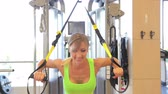 Young attractive woman does core abs crossfit oblique training with fitness trx straps in the gyms studio.