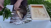 aluminium dishes : onion leaf parsley thyme spice put in huge fish prepared to bake in foil in fire ember. Stock Footage