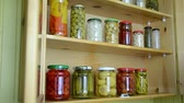 conservado : hand opens a wooden cupboards door and take all the jars from the underneath shelf