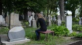 shrink : Depressed woman sit on bench near father grave in cemetery. Stock Footage