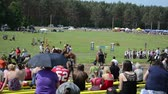 riot control : NIURONYS, LITHUANIA - JUNE 01: Panorama of people watch various riders in annual public horse festival on June 01, 2013 in Niuronys, Lithuania. Stock Footage