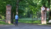 bike ride : Woman girl ride bike bicycle through old retro red brick gates to the green park area. Stock Footage