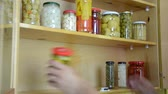 conservado : hand take from shelves in kitchen cupboard different size jars with marinated vegetables