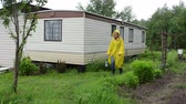 movable : Woman with yellow waterproof raincoat coat walk in garden near small movable house. Stock Footage