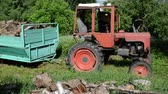 cabine : Farmer with hat exit tractor driver cabine and climb into trailer full of firewood.