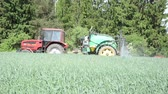 verdejante : a farmer driving a tractor with a long fertilizer spray nozzles along the forest