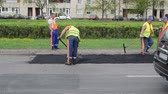 asphalt : VILNIUS, LITHUANIA - CIRCA MAY 2013 - workers with shovels put hot asphalt on street road holes and cars go circa May 2013 in Vilnius, Lithuania. Industrial street repair work.