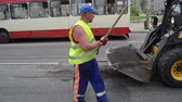 оставаться : VILNIUS, LITHUANIA - CIRCA MAY 2013 - Worker uniform clean asphalt remain with shovel and brush small rv bobcat and people in bus stop circa May 2013 in Vilnius, Lithuania.