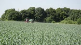 heavy : tractor with long spreading spray nozzles rides along forest spraying pesticides a large part of the field